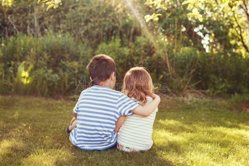 Niños que abrazan en el jardín en la puesta del sol foto de archivo libre de regalías