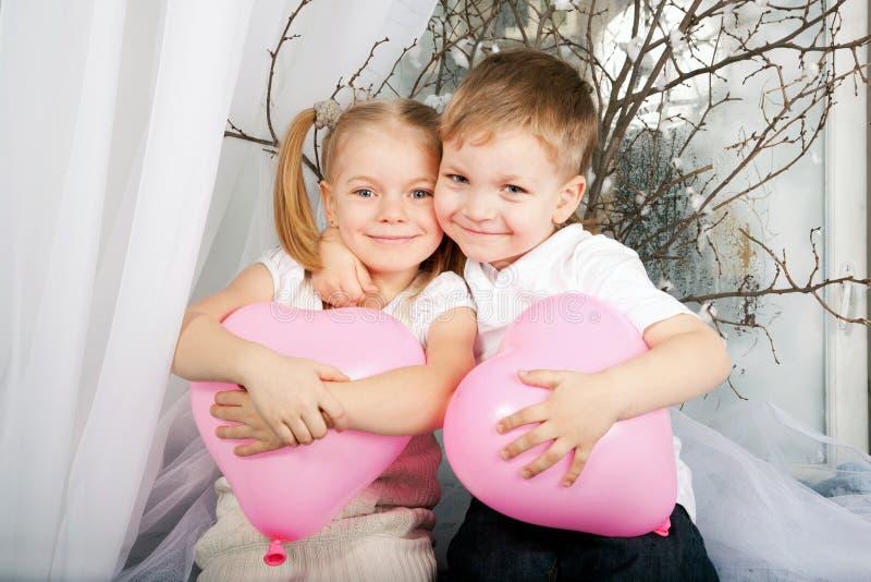 Niños que abrazan y que sostienen los globos del corazón. fotografía de archivo