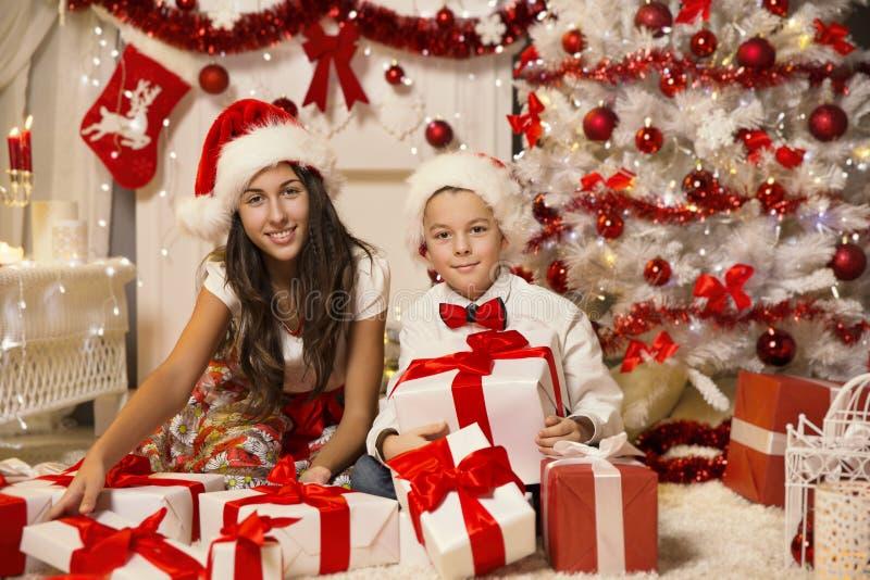 Niños que abren la caja de regalo del regalo de Navidad, celebrando al niño imágenes de archivo libres de regalías