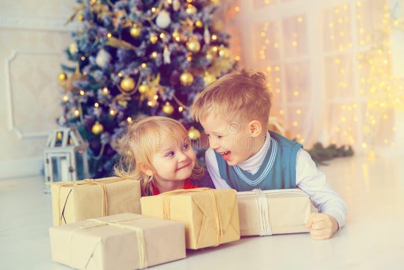 Niños que abren regalos de Navidad en sala de estar adornada imagen de archivo libre de regalías