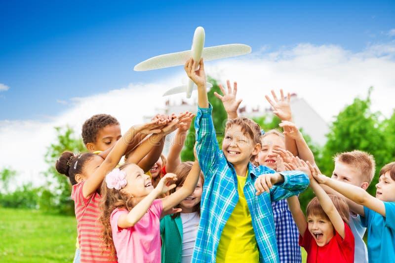 Niños que alcanzan después de juguete blanco grande del aeroplano foto de archivo