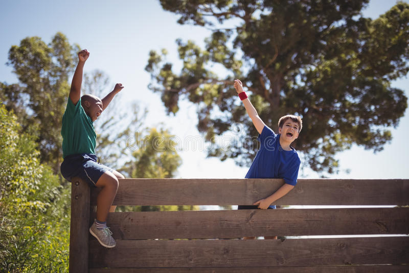 Niños que animan en la pared de madera durante carrera de obstáculos imagen de archivo