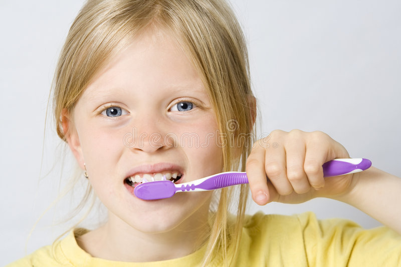 Niños que aplican los dientes con brocha imagen de archivo