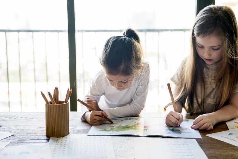 Niños que aprenden concepto de las muchachas del estudio imagen de archivo