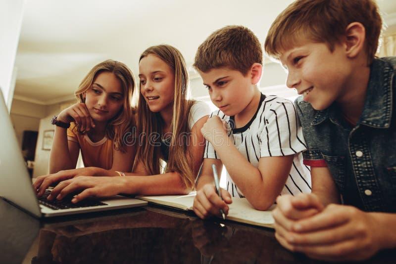 Niños que aprenden junto en un ordenador portátil imagenes de archivo