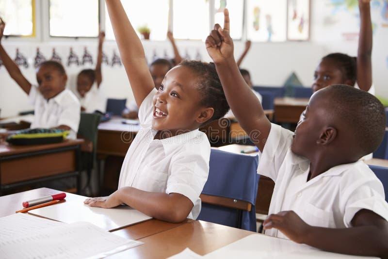 Niños que aumentan las manos durante la lección de la escuela primaria, cierre para arriba foto de archivo
