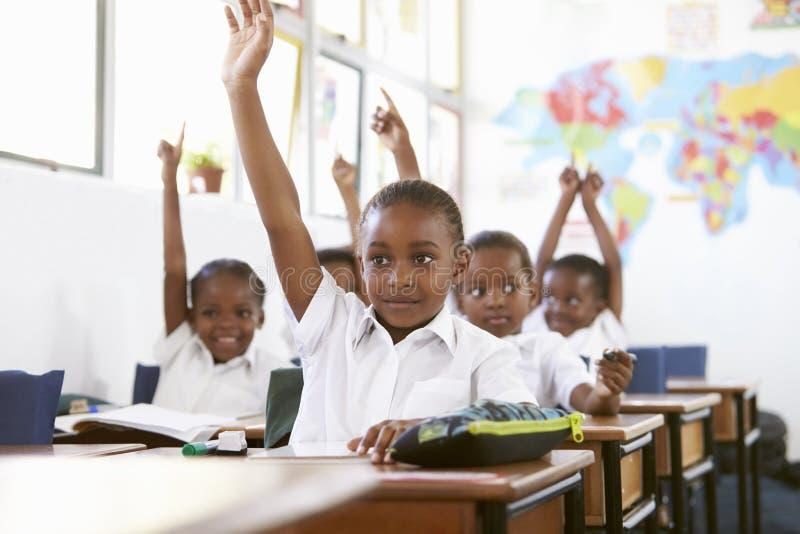 Niños que aumentan las manos durante una lección en una escuela primaria foto de archivo