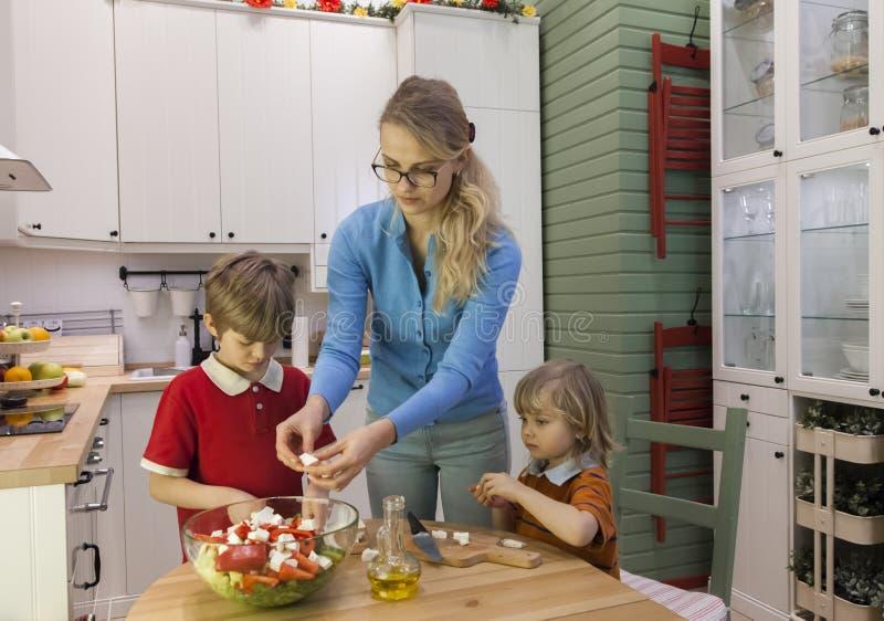 Niños que ayudan a la madre que prepara la ensalada vegetal imagenes de archivo