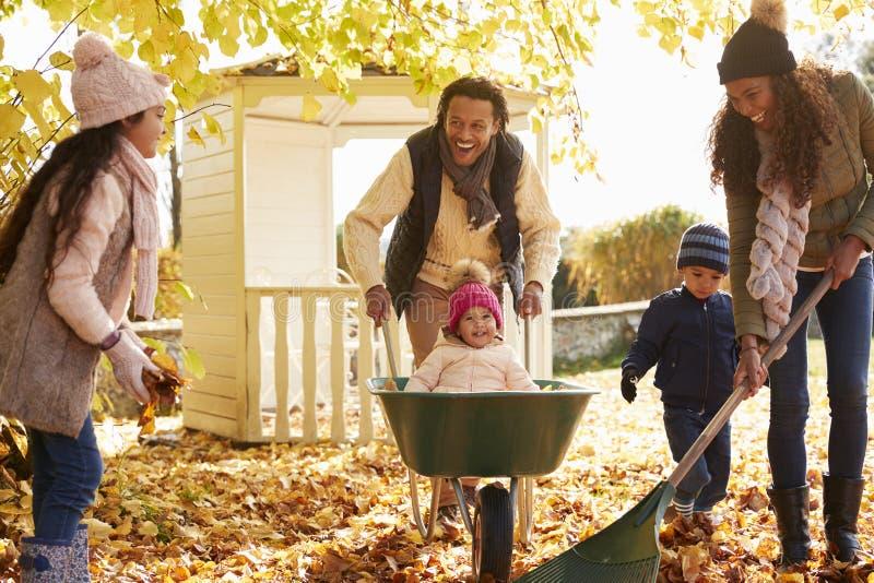 Niños que ayudan a padres a recoger a Autumn Leaves In Garden fotografía de archivo