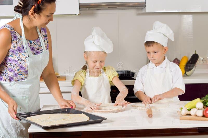 Niños que ayudan a su madre a preparar la pasta foto de archivo
