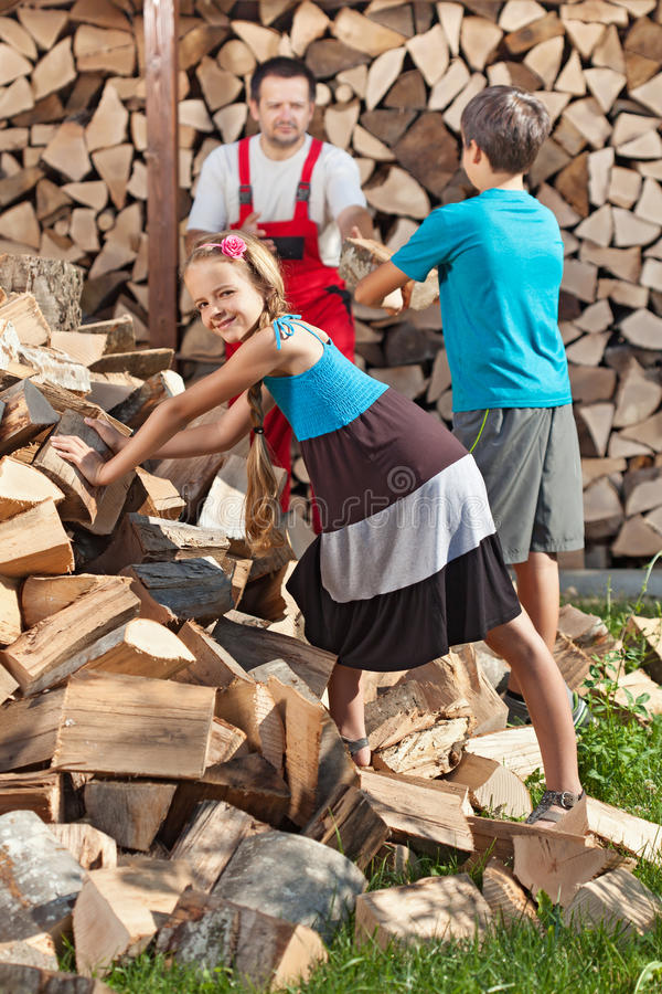 Niños que ayudan a su padre a apilar la leña tajada imagenes de archivo