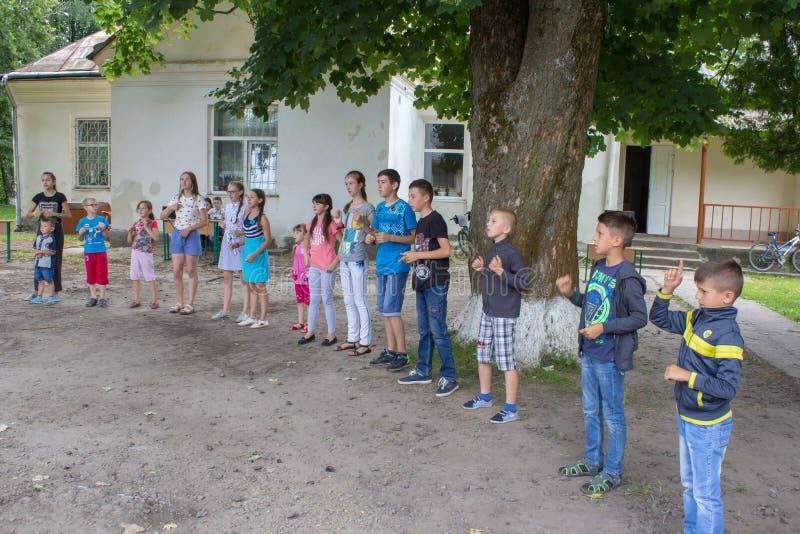 Niños que bailan en el campo, 6 07 2018 Ucrania Mervichi, los niños felices baila en un círculo en el campo imagenes de archivo