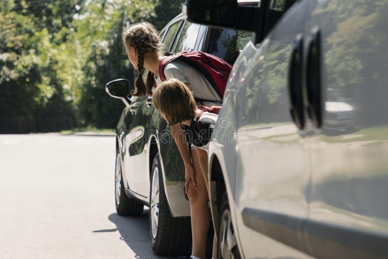 Niños que caminan a través del camino entre los coches fotografía de archivo libre de regalías