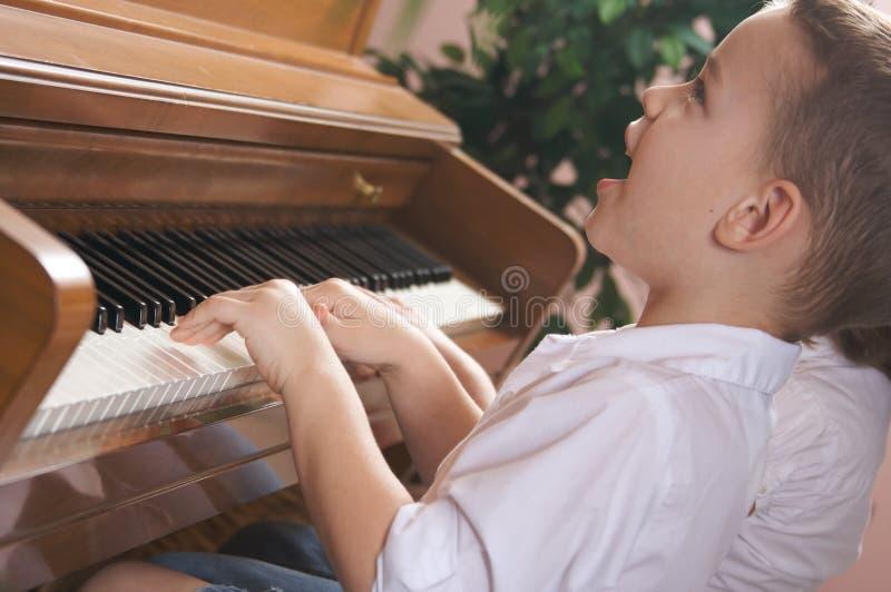 Niños que cantan y que juegan el piano fotografía de archivo