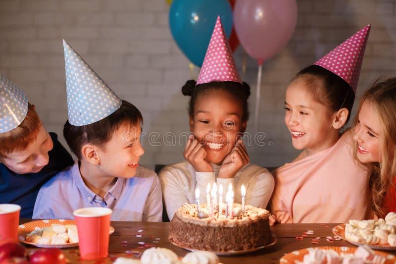 Niños que celebran el cumpleaños, mirando la torta con las velas imágenes de archivo libres de regalías