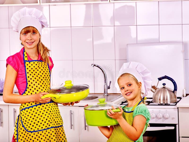 Niños que cocinan en casa la cocina Muchacha en sombrero del cocinero fotos de archivo