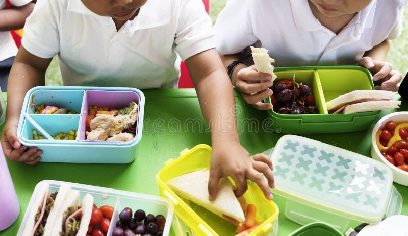 Niños que comen el almuerzo en la escuela primaria fotografía de archivo