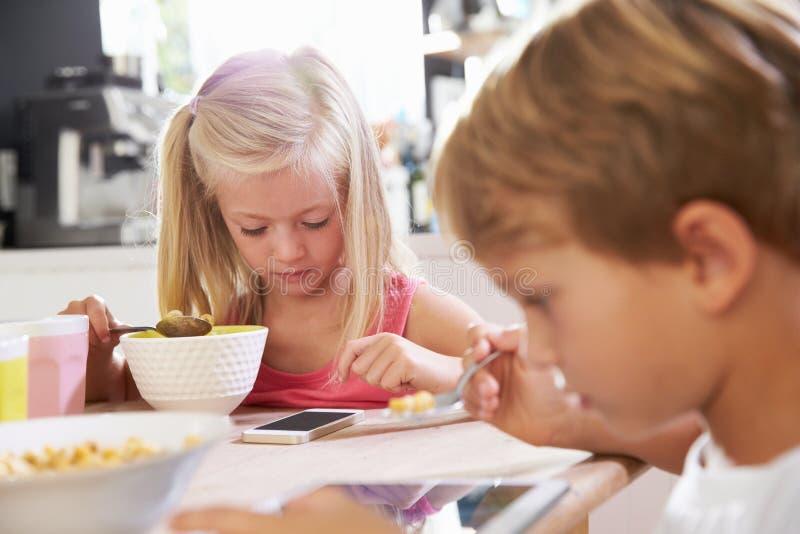 Niños que comen el desayuno mientras que juega con el teléfono móvil imagen de archivo libre de regalías