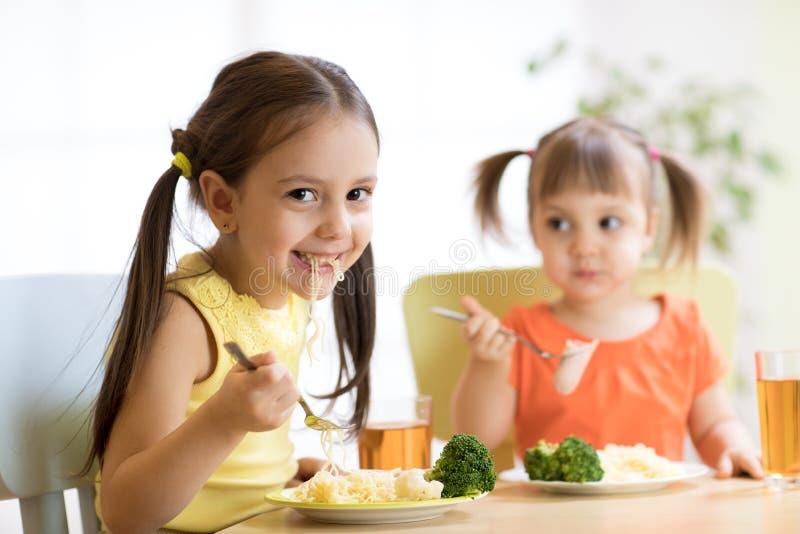 Niños que comen la comida sana en cuarto de niños o en casa imagenes de archivo