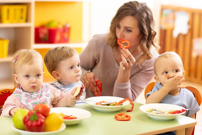 Niños que comen la comida sana en guardería, cuarto de niños o en casa imagen de archivo libre de regalías