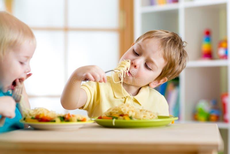Niños que comen la comida sana en guardería o foto de archivo