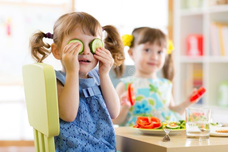 Niños que comen la comida sana en guardería o en casa imagen de archivo