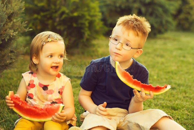 Niños que comen la sandía roja en hierba fotografía de archivo libre de regalías