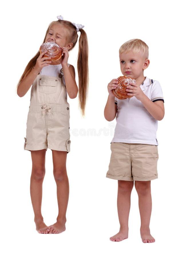 Niños que comen los pasteles aislados en un fondo blanco Hermano lindo y hermana que comen los bollos de canela Concepto hecho en fotografía de archivo