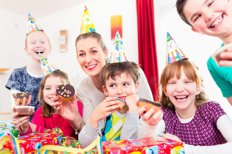 Niños que comen magdalenas que celebran cumpleaños imágenes de archivo libres de regalías
