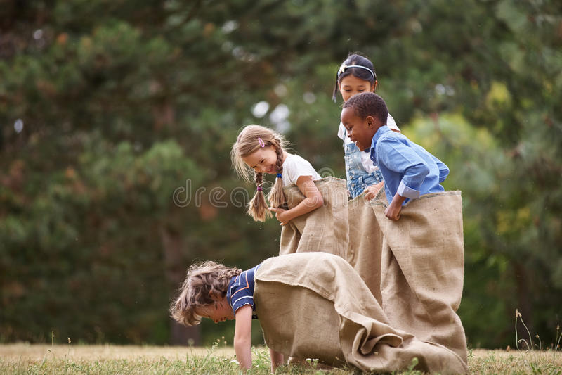 Niños que compiten en la raza de saco foto de archivo