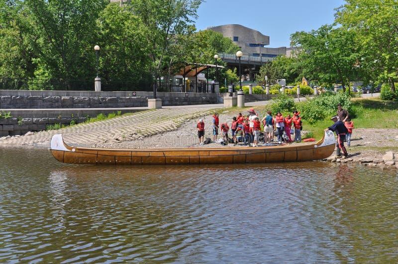 Niños que consiguen listos para un paseo de la canoa de Voyageur foto de archivo libre de regalías