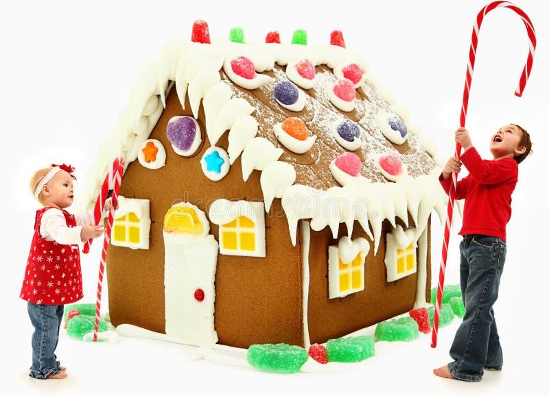 Niños que construyen el pan de jengibre gigante Hous de la Navidad foto de archivo libre de regalías