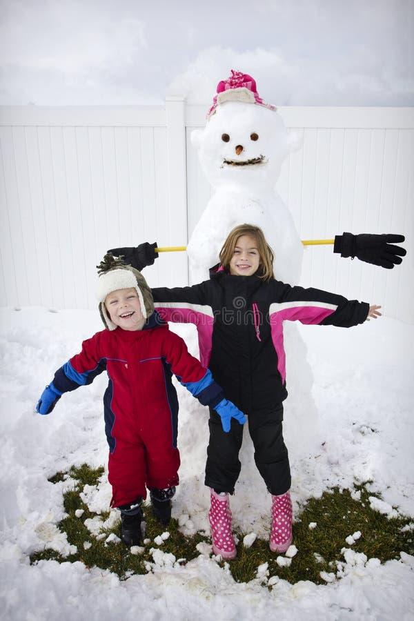 Niños que construyen un muñeco de nieve fotografía de archivo libre de regalías