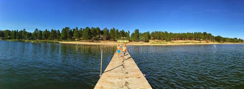 Niños que corren en un embarcadero en acampar del verano del lago fotografía de archivo libre de regalías