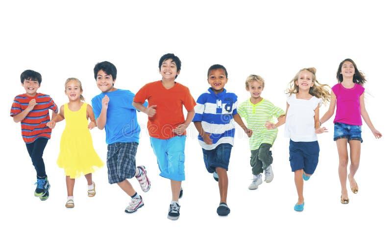 Niños que corren jugando junto concepto lindo del disfrute fotos de archivo libres de regalías