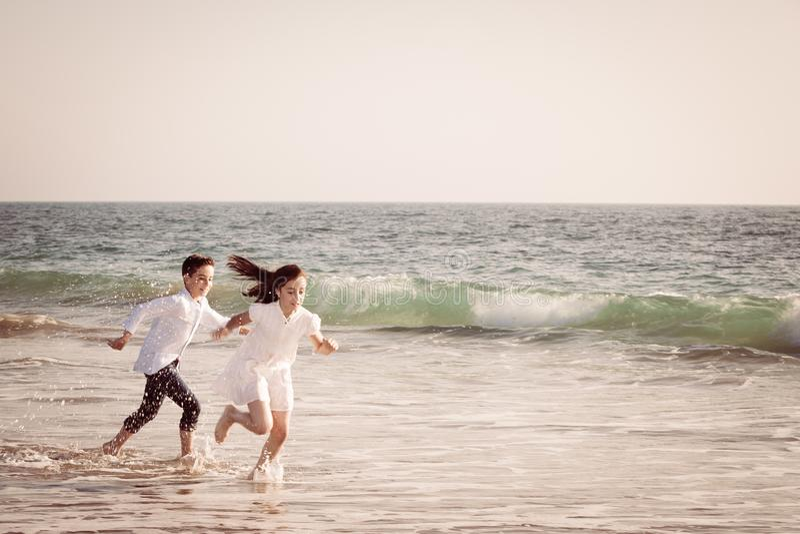 Niños que corren por la costa en los trajes blancos foto de archivo