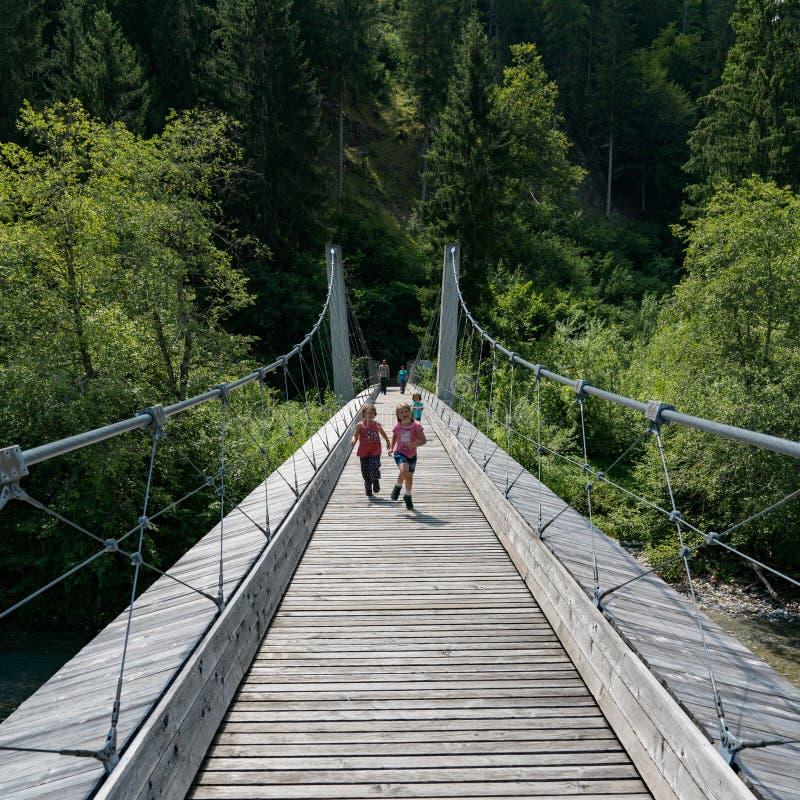 Niños que corren a través de puente colgante sobre el río Rhine en la garganta de Ruinaulta en las montañas suizas fotos de archivo