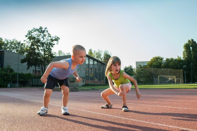 Niños que corren una carrera en el desierto imagenes de archivo