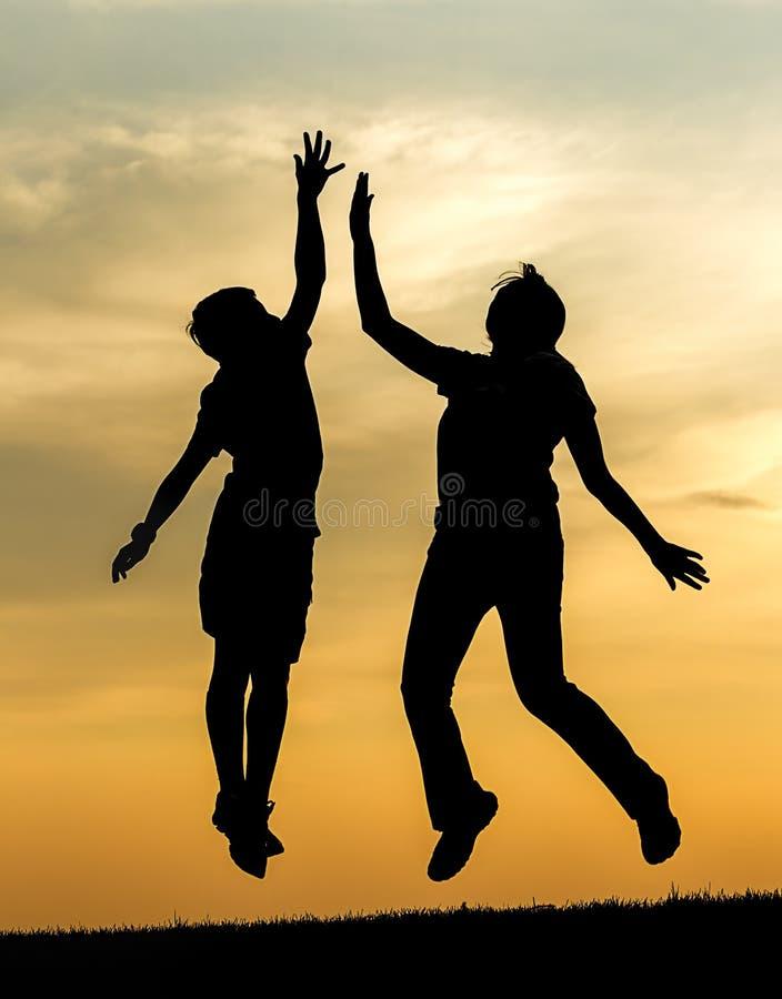 Niños que dan altos cinco en la puesta del sol fotos de archivo