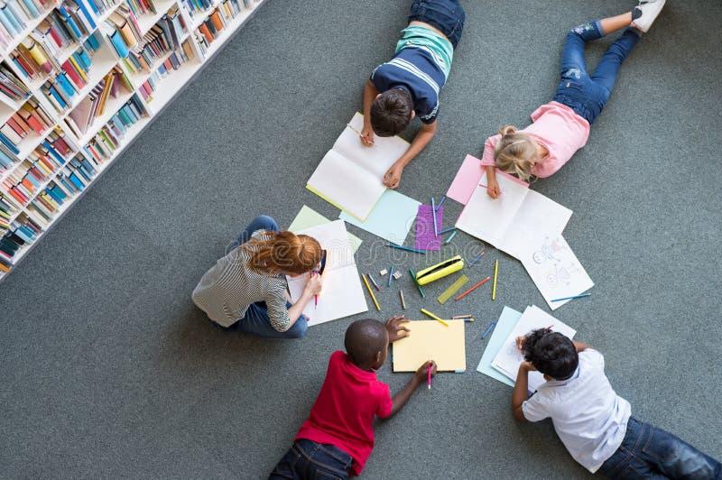Niños que dibujan en la biblioteca imágenes de archivo libres de regalías