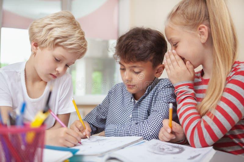 Niños que dibujan en la clase de arte de la escuela primaria imagenes de archivo