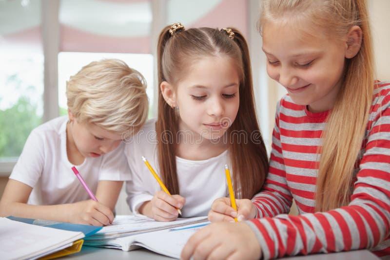 Niños que dibujan en la clase de arte de la escuela primaria fotos de archivo