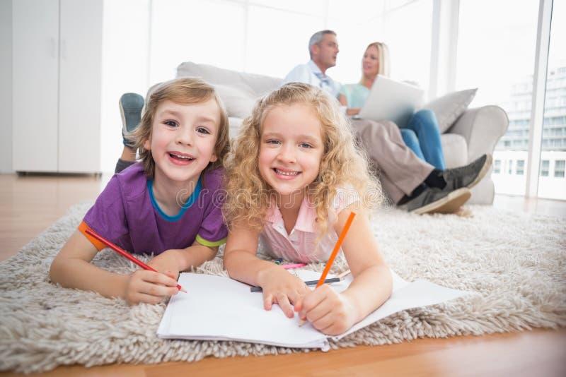 Niños que dibujan en los papeles mientras que padres que se sientan en el sofá foto de archivo
