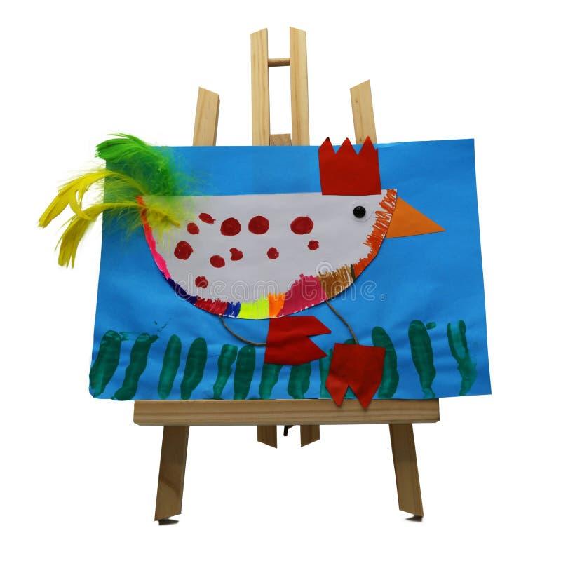 Niños que dibujan representando un pollo con las plumas coloreadas en el papel azul exhibido en un caballete de madera imagenes de archivo