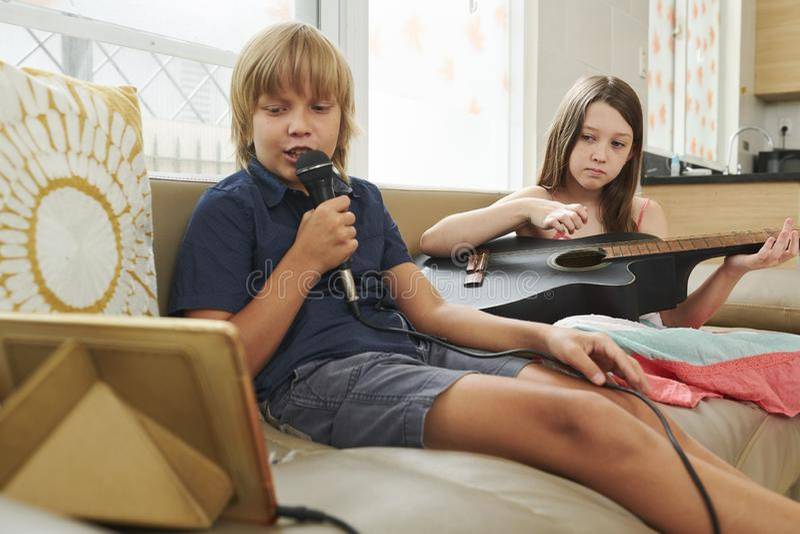 Niños que disfrutan de Karaoke en casa fotos de archivo libres de regalías
