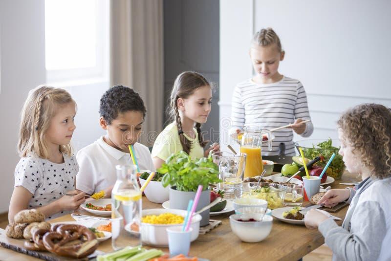 Niños que disfrutan de una comida sana por una tabla en un dur del comedor imagenes de archivo