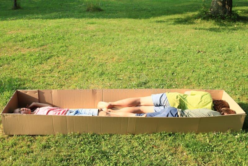 Niños que duermen en una caja imagen de archivo