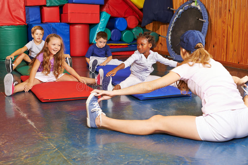 Niños que ejercitan en la educación física imagenes de archivo