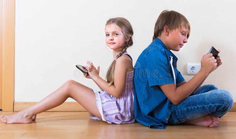 Niños que entierran en teléfonos móviles fotos de archivo