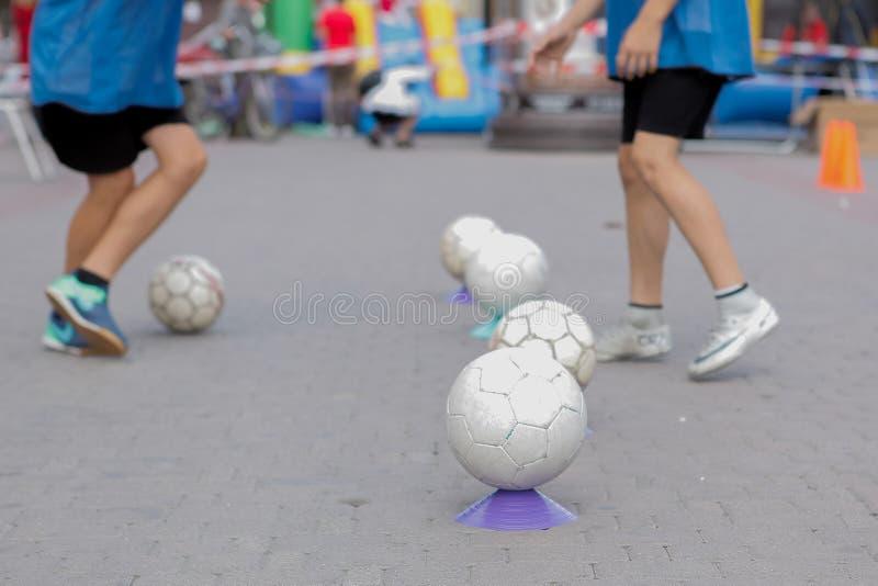 Niños que entrenan en la academia del fútbol, entrenamiento del ` s de los niños con las bolas fotografía de archivo